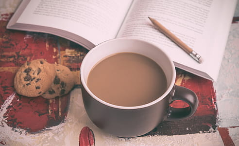 black mug filled with coffee beside open book and chocolate chip cookies