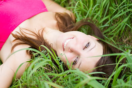 woman in pink strapless shirt lying on grass field during daytime
