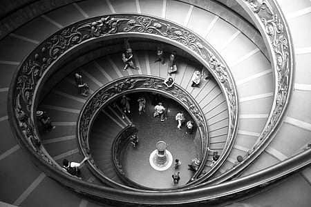 gray scale photography of group of people in twirl staircase