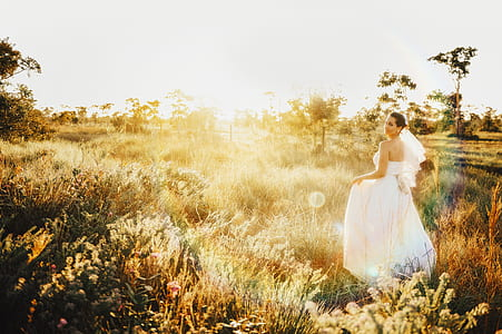 photo of bride standing on brown grass field