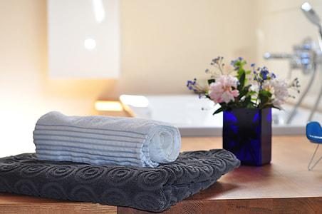 white textile on brown bathroom towel