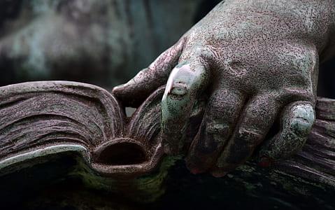 person holding book statue