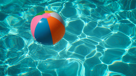 blue, pink, and orange inflatable ball on body of water