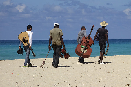 people carrying instruments on beach