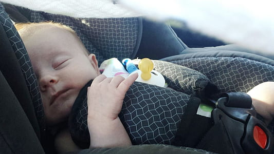 baby sleeping on grey vehicle booster seat