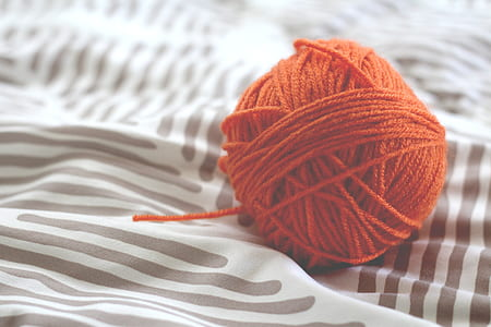 red yarn ball on top of blue and white striped textile
