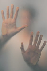 photo of person touching frosted glass
