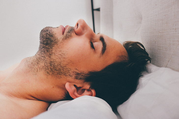 man sleeping on white bed