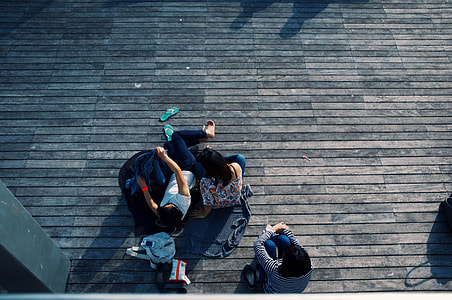 3 people sitting on brown wooden floor at daytime
