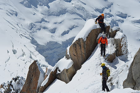 three person on snow-covered mountain during daytime