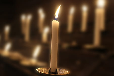 lighted white candle on grey candle holder