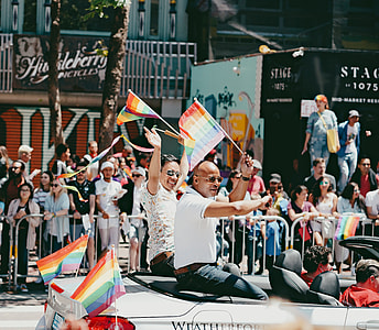 two men riding a convertible coupe holding LGBT flaglets during daytime