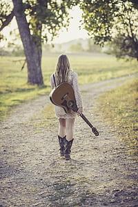 walking woman holding brown guitar at daytime
