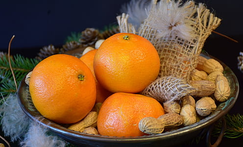 four orange fruits on bowl