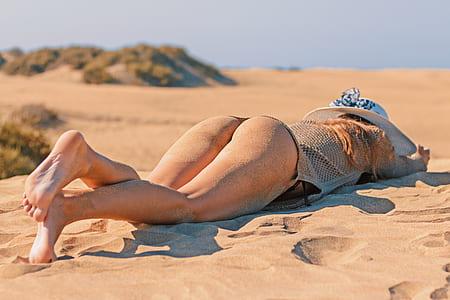 woman wearing bikini lying on seashore