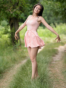 woman wearing pink sleeveless mini dress standing on green grass