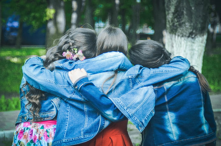 photo of three girls with denim jackets