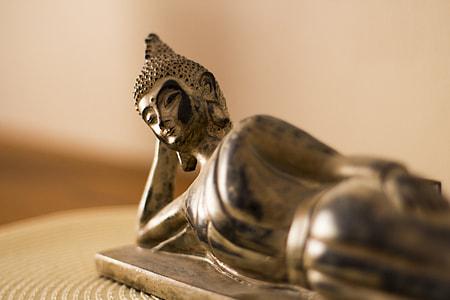 selective focus photography of leaning Gautama Buddha figurine