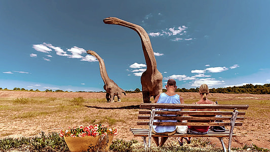 person sitting on brown bench with brontosaurus