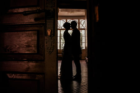 man and woman standing face to face in brown painted room