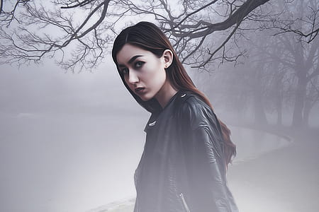 woman wearing black leather jacket standing in dark foggy forest