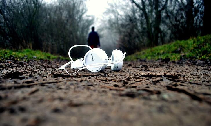 white headphones on brown road