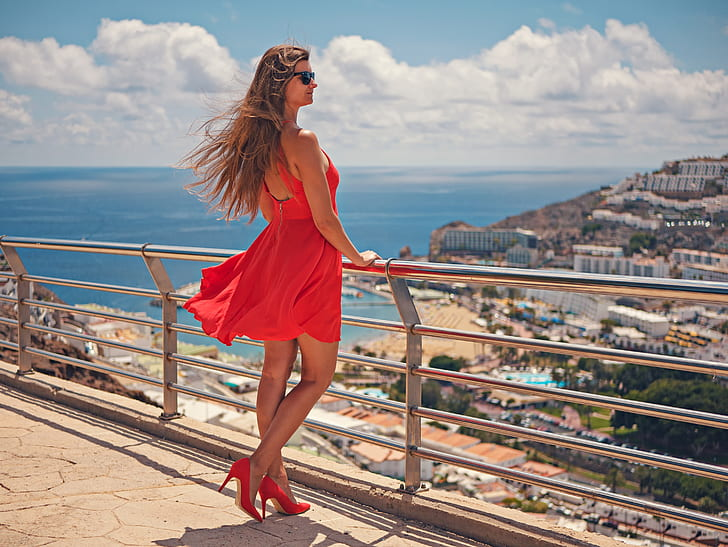 woman in red halter dress standing at the bridge