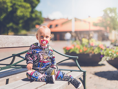 toddler sitting on gray wooden bench