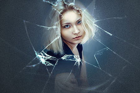 woman with platinum hair looking at broken glass
