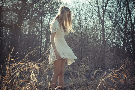 woman in white dress standing in withered forest