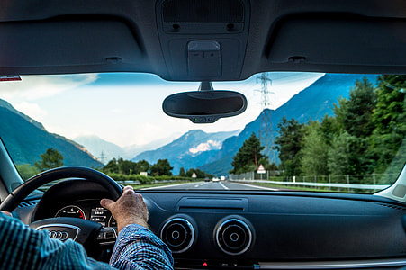 Man driving a car on road in the mountains of Switzerland