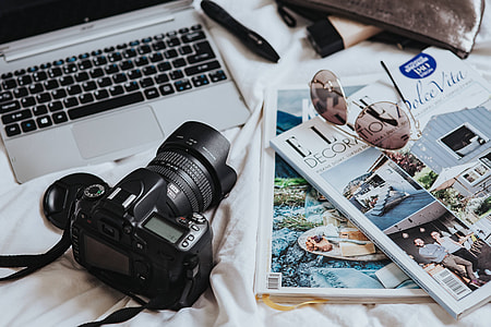 Silver laptop, a camera, magazines and other items on white bed sheets