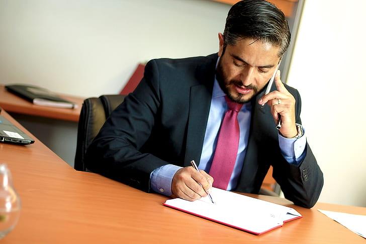 man with black suit jacket holding pen