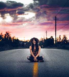 selective focus photography of woman sitting in the middle of the road