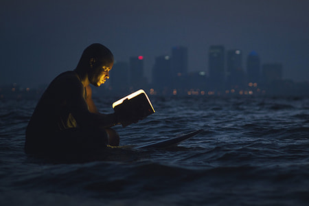 Man reading a book in the ocean at night