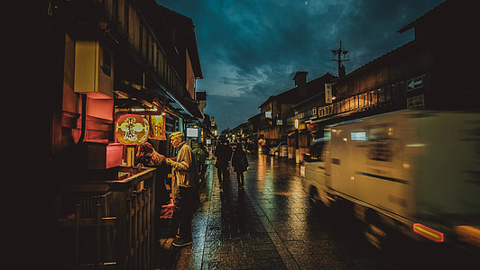 man standing near food stall at night time
