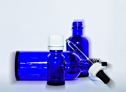 three blue glass bottles with dropper closeup photo