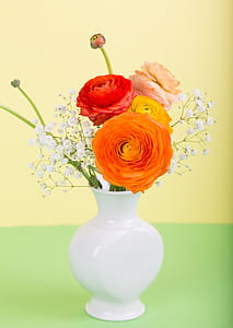 variety of flowers in vase with yellow background