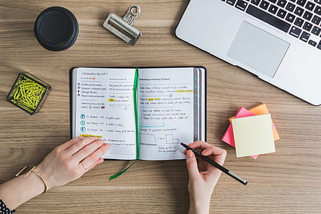 woman writing on a planner beside silver MacBook
