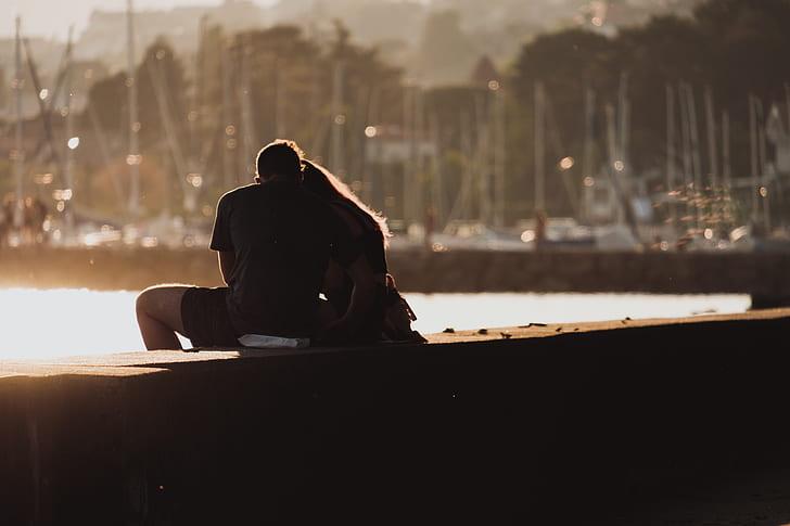 couple sitting on harbor during daytime