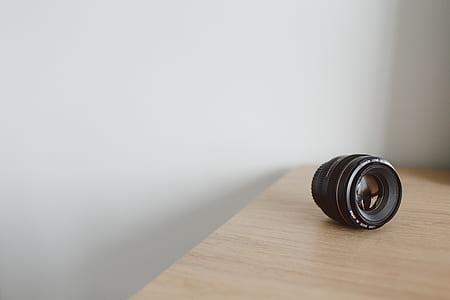 black DSLR camera lens on brown wooden surface