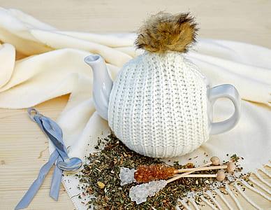 white ceramic teapot on textile