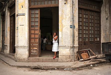woman near brown wooden door