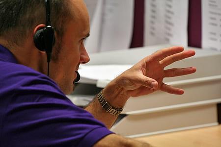 man in purple top doing hand gesture
