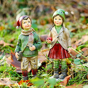 girl and a boy in green and red bobble hat figurines