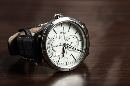 round silver-colored framed chronograph watch with black leather strap on brown wooden surface