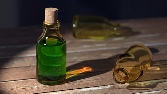 amber glass bottle with green fluid on brown surfa ce