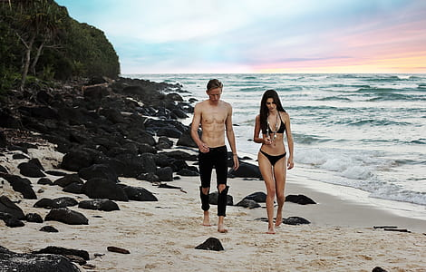 man and woman walking on seashore