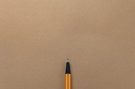 yellow ballpoint pen on beige surface