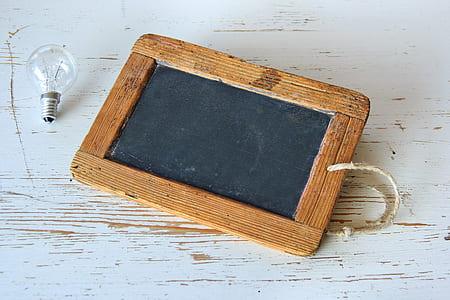 brown wooden photo frame beside bulb